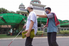 Two blind men walk to the Nurul Ihsan Mosque in Pondok Ranggon, East Jakarta, Friday, Sept. 11, 2020 to perform Friday prayers. The Jakarta administration has reimposed full large-scale social restrictions (PSBB) starting on Sept. 14, 2020. Places of worship in residential areas and housing complexes are allowed to remain open at 50 percent capacity. Larger houses of worship and those located in COVID-19 red zones are required to close. JP/P.J. Leo