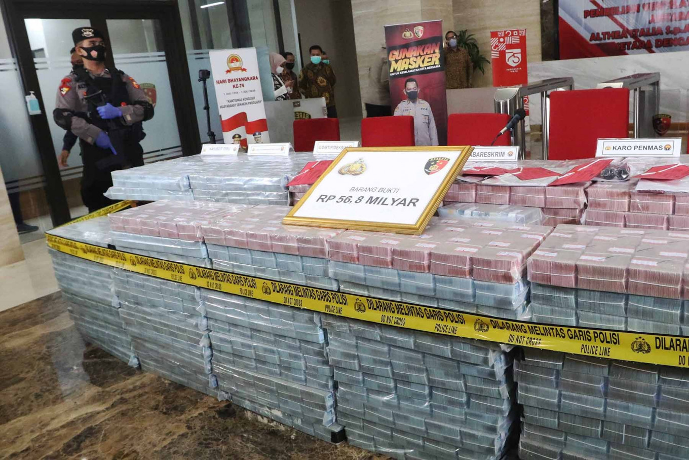 Police officers guard stacks of cash totaling Rp 56.8 billion that were seized as  evidence in a fraud case involving the purchase of ventilators at the National Police Headquarters in Jakarta, Sept. 7, 2020. Bareskrim head Comr. Gen. Listyo Sigit Prabowo said a syndicate had stolen money transferred under a contract of sale between two foreign healthcare technology firms: Althea Group from Italy and Shenzhen Mindray Bio-Medical Electronics from China. JP/Dhoni Setiawan