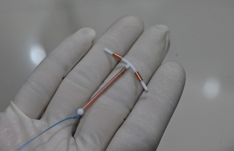Up close: A doctor holds an IUD birth control device at a clinic in Jakarta. During the pandemic, some 10 percent of Indonesia's 28 million family planning participants have faced problems accessing birth control.