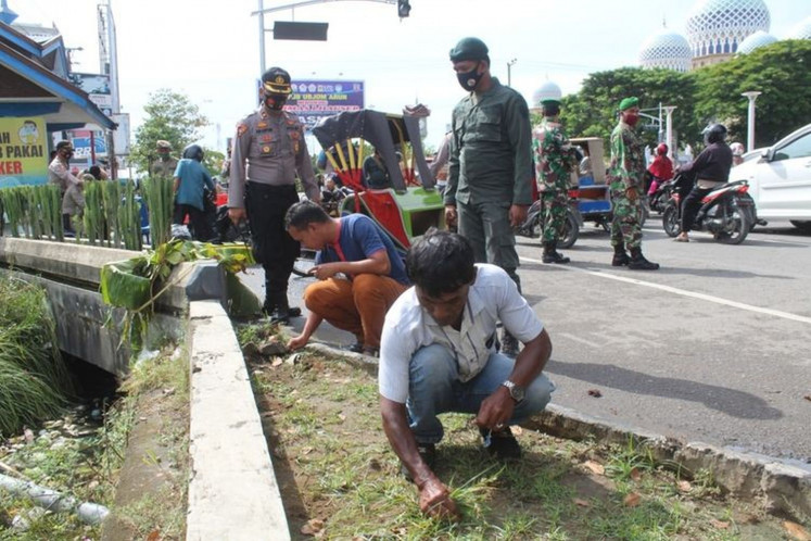 Local residents in Lhokseumawe, Aceh, who violate COVID-19 health protocols are ordered to clean a city park by pulling the weeds by local authorities on Sept. 14.