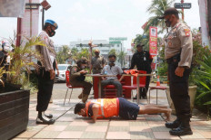 A man is forced to do push-ups by joint security task force personnel on Friday, September 18. 2020 as punishment for his failure to wear a mask. The public punishment was part of a police operation designed to enforce COVID-19 health protocols in Cinere, Depok, West Java. Violators of the protocols are subject to fines or non-judicial punishments such as sweeping the roads, singing national songs or doing push-ups. JP/Dhoni Setiawan