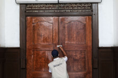 A mosque security guard locks the doors of Cut Meutia Mosque in Central Jakarta on Thursday, September 17, 2020. The city administration has reimposed full large-scale social restrictions to combat a COVID-19 spike in the capital that has strained hospital resources. JP/Seto Wardhana