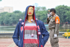 A Jakarta Public Order Agency official stands guard near a mannequin reminding people about the danger of COVID-19 in Sunter, North Jakarta, on Tuesday, September 15. 2020. JP/Seto Wardhana