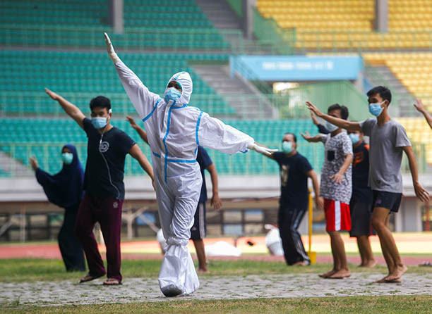 A health worker wearing protective suit and patients exercise at the Patriot Chandrabhaga Stadium which has been converted into a quarantine house amid the coronavirus disease (COVID-19) outbreak, in Bekasi, West Java, on Sept. 28.