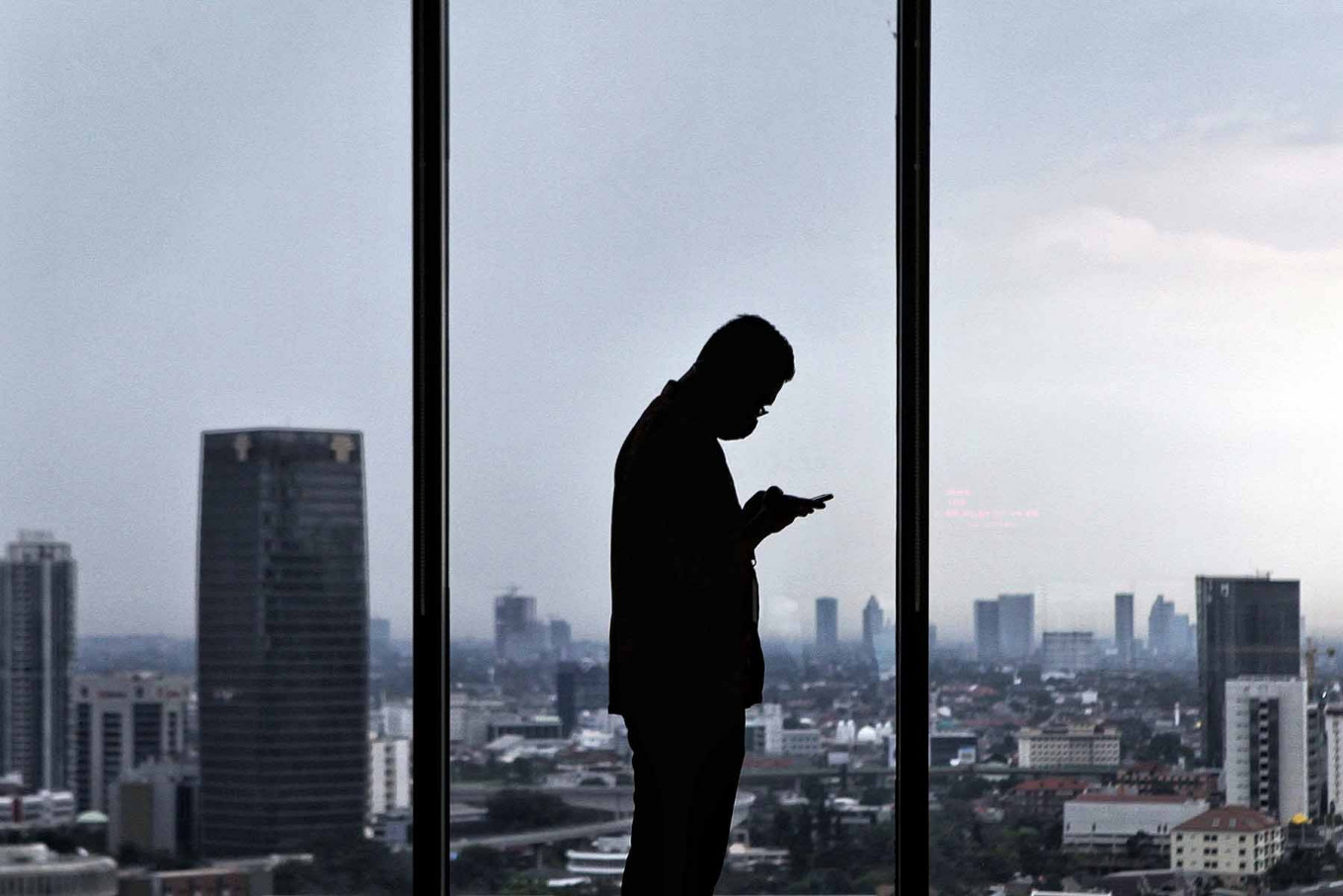 A Muamalat Bank employee uses his smartphone at work at the Muamalat Tower in Jakarta on Sept. 22. Finance Minister Sri Mulyani projects that Indonesia's economy will contract between 0.6 to 1.7 percent this year due to the COVID-19 pandemic. JP/Seto Wardhana.