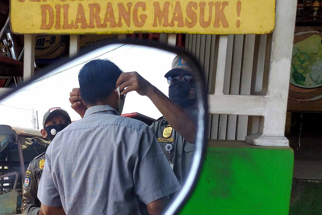 A Public Order Agency (Satpol PP) officer puts a face mask on a man during a security operation in Depok, West Java, on Sept 23. A joint security task force punishes anyone caught not wearing a mask by making them wear an orange vest and recite state ideology Pancasila. JP/PJ Leo
