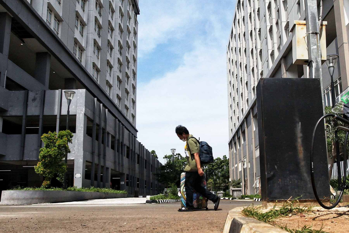 A man leaves Pademangan Athletes Village in North Jakarta, Sept. 25. The government plans to use a tower in Pademangan Athletes Village for asymptomatic COVID-19 patients if the isolation ward in the adjacent Kemayoran Athletes Village is full. JP/Seto Wardhana