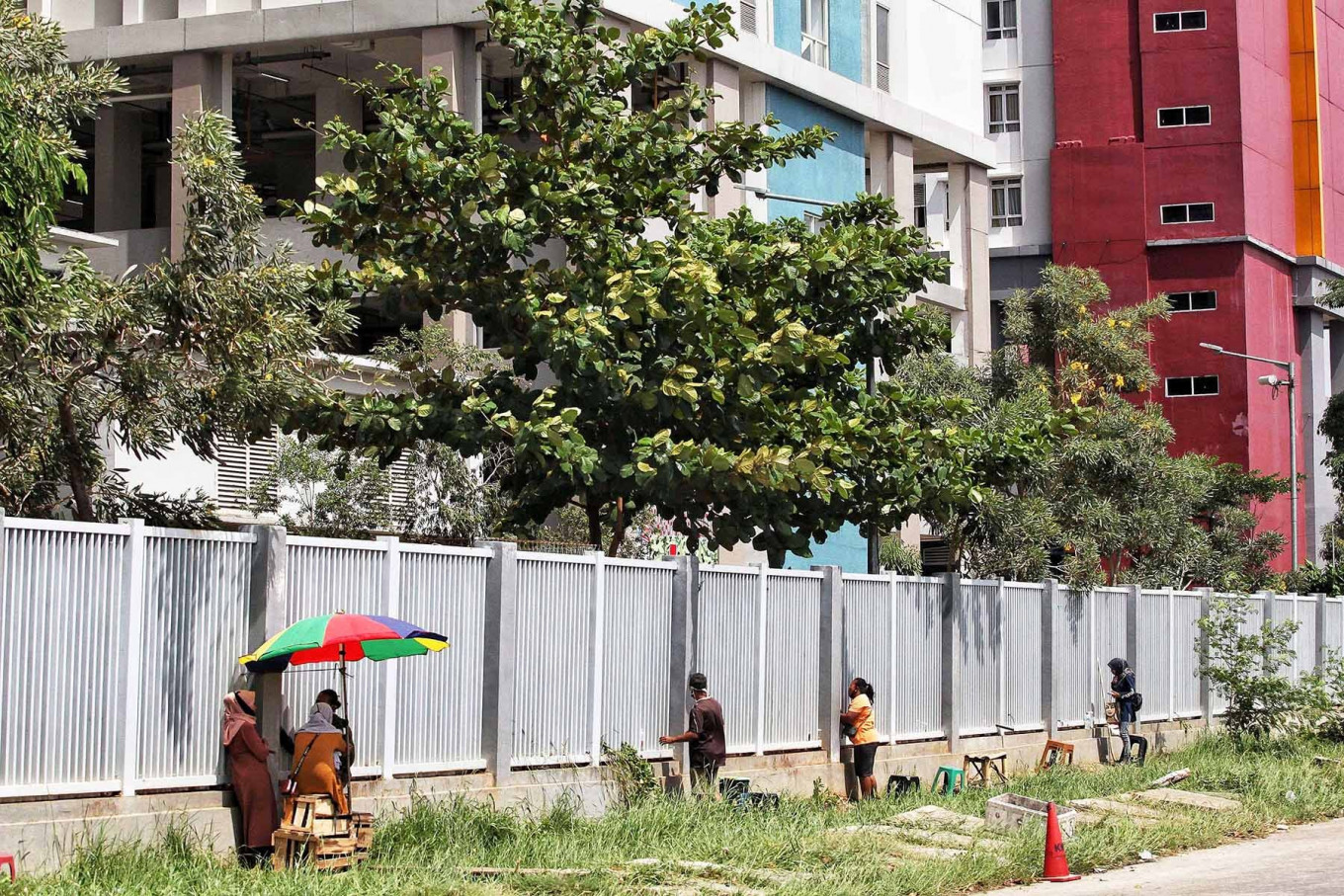 Street vendors serve customers behind the fence of Pademangan Athletes Village in North Jakarta on Sept. 25. The facility accommodates repatriated Indonesians who have been quarantined for suspected COVID-19 infection. JP/Seto Wardhana
