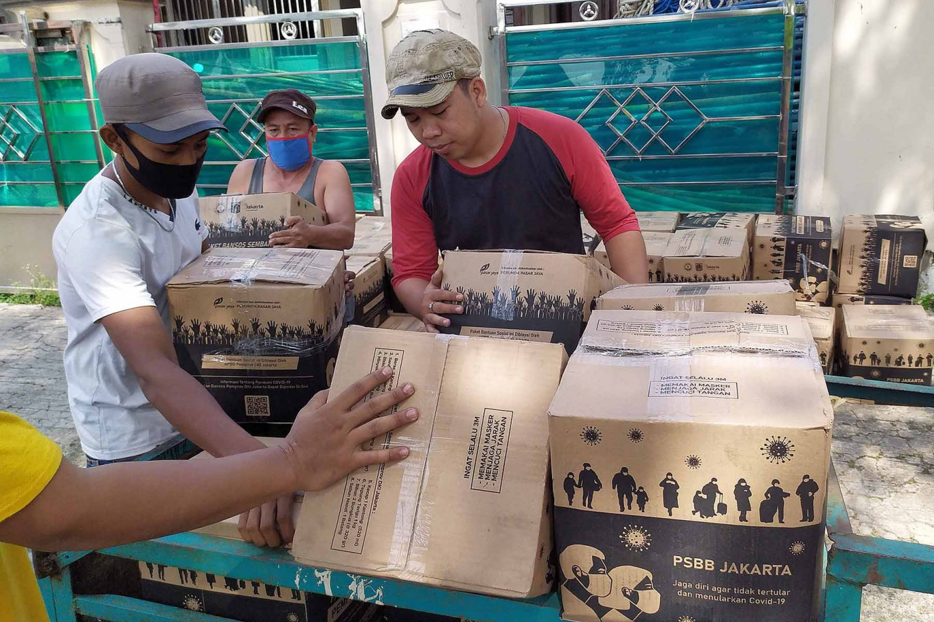 Residents distribute staple food to their neighbors in Tengah subdistrict, Kramat Jati, East Jakarta on Sept. 25. The Jakarta administration is distributing grocery packages to low-income families as the administration reinstates the large-scale social restrictions (PSBB). JP/PJ Leo