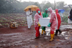 Workers carry the coffin of a COVID-19 victim amid heavy rain at Pondok Ranggon public cemetery in East Jakarta on October. 2. 2020. The Jakarta administration has begun the two-month project of expanding the burial area for COVID-19 patients. In the first phase of expansion, the administration cleared 7,141 square meters. JP/PJ Leo