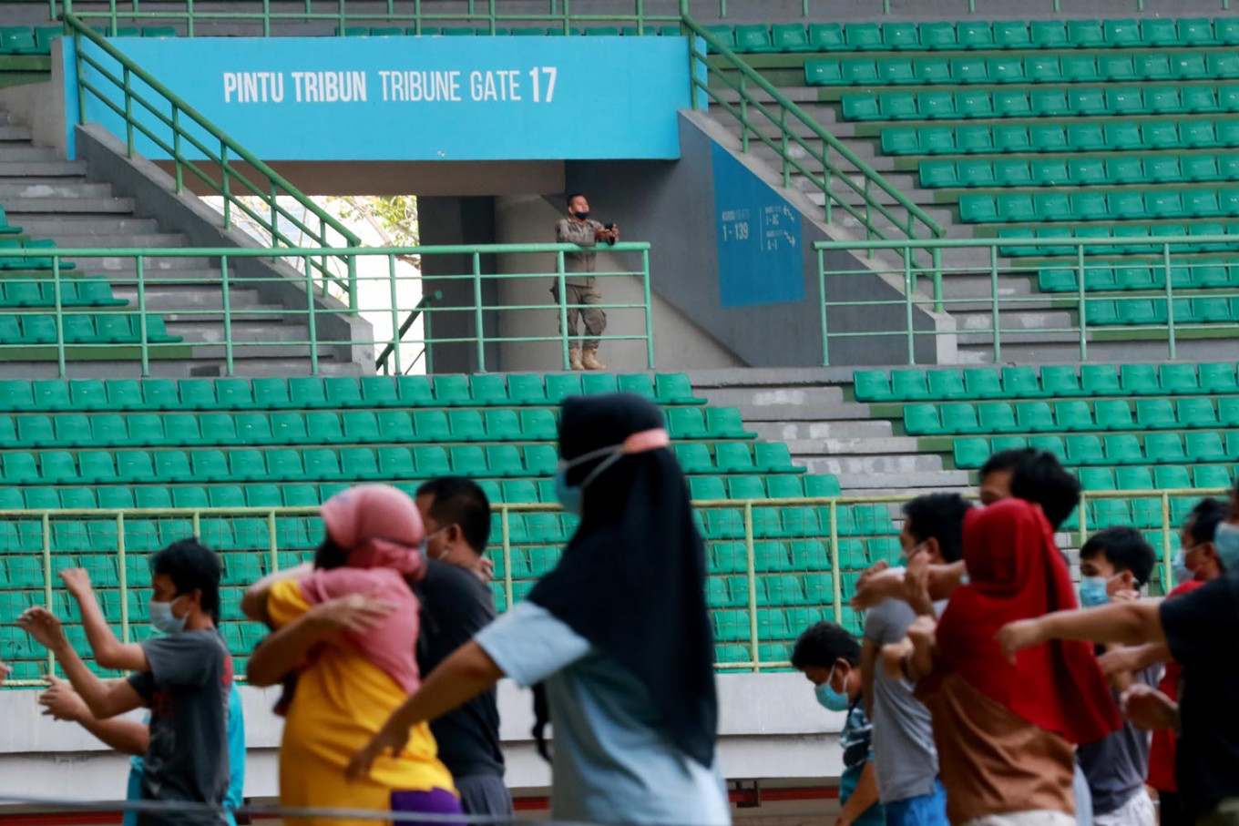 A Bekasi Public Order Agency (Satpol PP) officer watches over the morning exercises for asymptomatic COVID-19 patients isolating at the Patriot Candrabhaga Stadium isolation center in Bekasi, West Java, on October. 2. 2020. The stadium houses asymptomatic patients whose homes do not have sufficient space for self-isolation. JP/Dhoni Setiawan