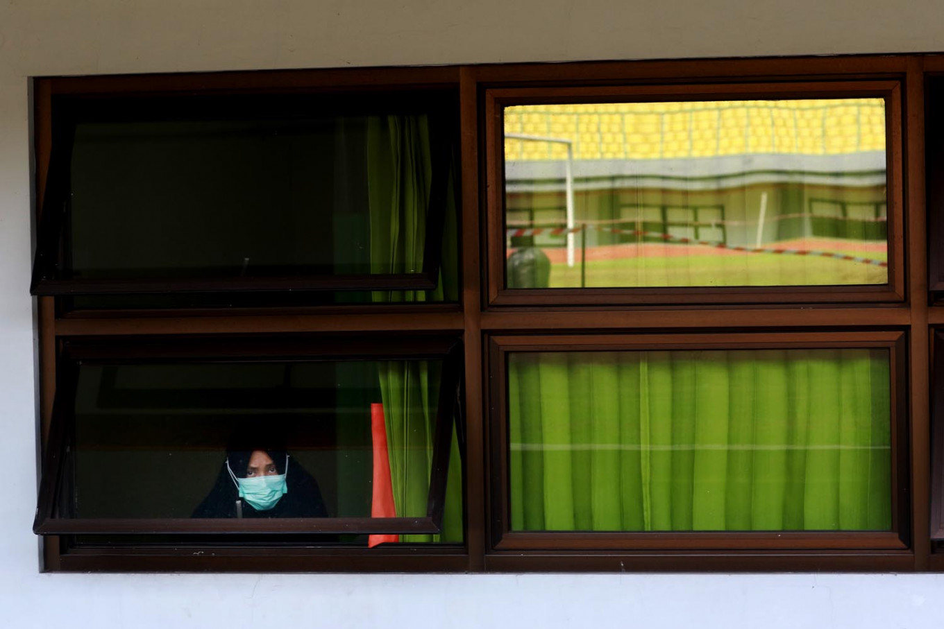 An asymptomatic COVID-19 patient looks out the window while undergoing isolation at the Patriot Candrabhaga Stadium isolation center in Bekasi, West Java on October. 2. 2020. The isolation ward at the stadium has the capacity to house 55 patients. JP/Dhoni Setiawan