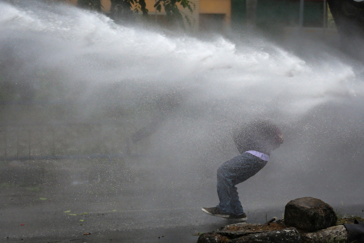 A protester gets sprayed by water from a canon in jl> Daan Mogot in Tangerang on Oct. 8 during a rally against the passing of the Job Creation Law.