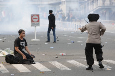 Cause for tears: A protesters sits in a road as tear gas fired by police obscures the scene behind him during a demonstration on Thursday, October 8. 2020 in Harmoni, Central Jakarta. Labor unions, students and members of the general public have been up in arms since Monday, when the House of Representatives gave its final approval for passing the job creation omnibus bill into law. JP/Wendra Ajistyatama