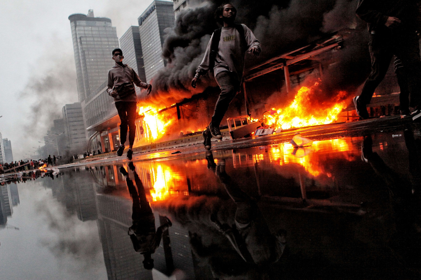 Up in flames: Protesters run past the Hotel Indonesia Transjakarta bus shelter in Central Jakarta as it is engulfed by a fire during a demonstration on Thursday, October 8. 2020 that turned violent. Nationwide demonstrations since Tuesday have demanded the immediate revocation of the Job Creation Law. JP/Seto Wardhana