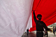 Divided nation: A student walks beneath a large Indonesian flag on Thursday, October 8. 2020 during a protest against the newly passed Job Creation Law on Jl. M.H. Thamrin in Central Jakarta. JP/Seto Wardhana