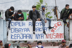 "(Not) on the fence: Protesters sit on a wall above a banner during a peaceful demonstration on Thursday, October 7. 2020 in Harmoni, Central Jakarta. The banner gives voice to the protesters' sense of public betrayal, pointing out that it is the people that elect and pay the salaries of lawmakers, only for them to ""cause trouble"". JP/Wendra Ajistyatama"