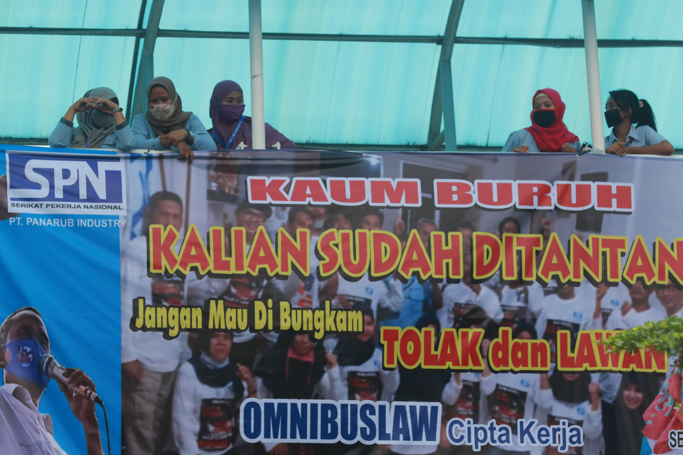 "Putting their foot down: Members of a factory union stand behind a banner protesting the recently passed omnibus bill on job creation during a strike on Wednesday, October 7.2020 at the sports footwear factory of PT Panarub Industry in Tangerang. The banner calls on workers to answer to the ""challenge"": ""Don't let them silence you. Reject and challenge the omnibus law on job creation."" JP/Dhoni Setiawan"