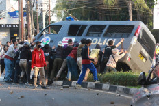 Tipping point: Student protesters overturn a police van during a protest on Wednesday, October 7. 2020 in Pejompongan, Central Jakarta. Demonstrations have taken place in major cities across the country from Tuesday to Thursday to protest the omnibus bill on job creation, which was passed on Monday. JP/Dhoni Setiawan
