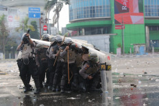 Close quarters: A policeman fires tear gas as other police officers take cover behind their shields on Thursday, October 8. 2020 during a protest in Harmoni, Central Jakarta. Civil society and rights groups on Thursday called on police to follow procedure and avoid using excessive force in dispersing protesters. JP/Wendra Ajistyatama