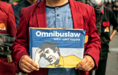 "Severe migraine: A student protester holds up a poster based on the packaging design of a headache medicine on Thursday, October 8. 2020 during a demonstration on Jl. M.H. Thamrin in Central Jakarta. The poster reads: ""The omnibus law causes headaches, environmental damage, workers' oppression."" JP/Seto Wardhana"
