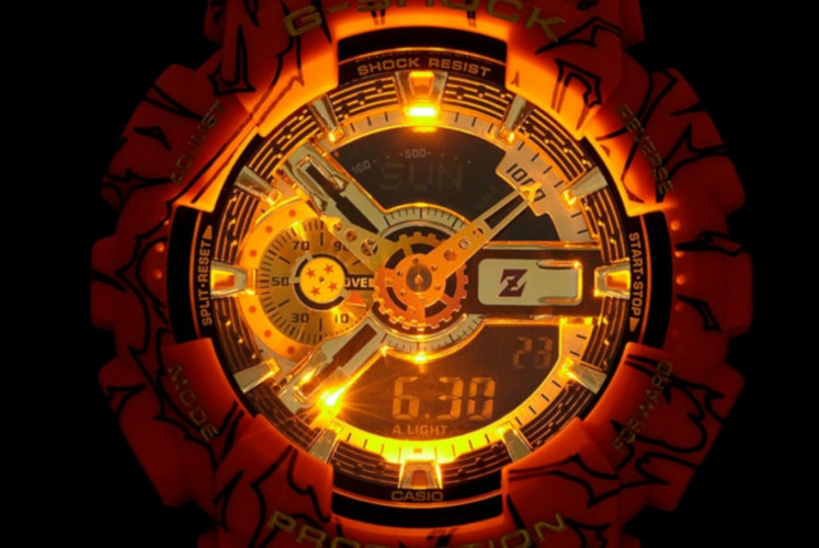 The watch's dial and logo are embellished with gold accent for a striking, fire effect, especially when the light is on.