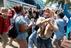 Workers of PT Panarub Industry sports footwear factory dance during a protest held in front of the factory in Tangerang, Banten, on Oct. 7. The workers voiced their concerns over the newly passed Job Creation Law during the protest. JP/Dhoni Setiawan