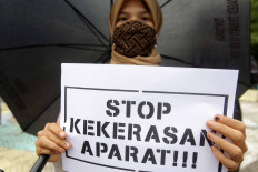 An activist from the Alliance Refusing to Forget (Aliansi Menolak Lupa) stands under a black umbrella in a silent protest in front on the Tugu Proklamasi (Proclamation Monument) in Central Jakarta, on Oct. 15. The activists protested against the police's repressive actions toward protesters during a series of rallies against the newly passed Job Creation Law. They called on the police to release detainees. JP/Wendra Ajistyatama
