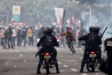A protester runs toward police officers who stand guard on motorcycles during a clash in Jakarta on Oct. 13. A series of protests took place across the country following the House of Representatives' decision to pass the jobs creation bill into law on Oct. 5. JP/Seto Wardhana