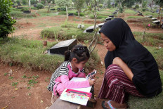 Adinda Rahma Barokah, 7, squats near a tombstone while doing her school assignment in Padurenan cemetery in Bekasi, West Java, on Oct. 15. She read the questions on her mother's phone and wrote down the answers in her notebook. As her school -- SD Wanarasi 15 state elementary school -- is closed due to the outbreak, Adinda has been studying in the cemetery where her mother sells snacks and drinks. JP/P.J.Leo
