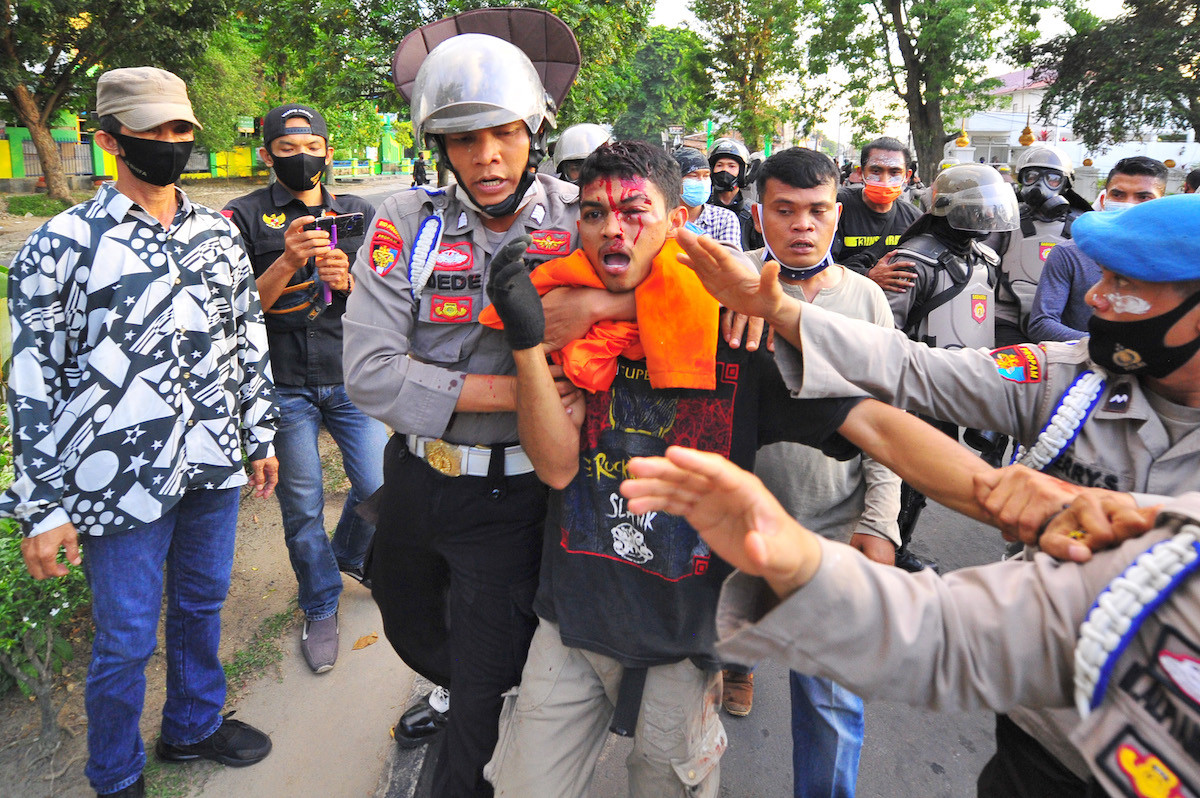 Police mistakenly beat undercover cop during Jambi jobs law protest