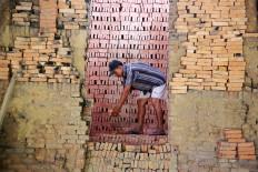 Minan, a brick maker from South Cikarang district in Bekasi, West Java, arranges bricks to be baked in a furnace on Oct. 23. JP/P.J.Leo