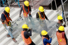 Workers carefully carry a glass plate at Jakarta's oldest high-rise building, Sarinah, on Oct. 30. The iconic shopping center is undergoing a major renovation, costing Rp 700 billion (US$47.9 million). The project is expected to be completed on Aug. 17, 2021, coinciding with Sarinah's 59th anniversary. JP/Dhoni Setiawan