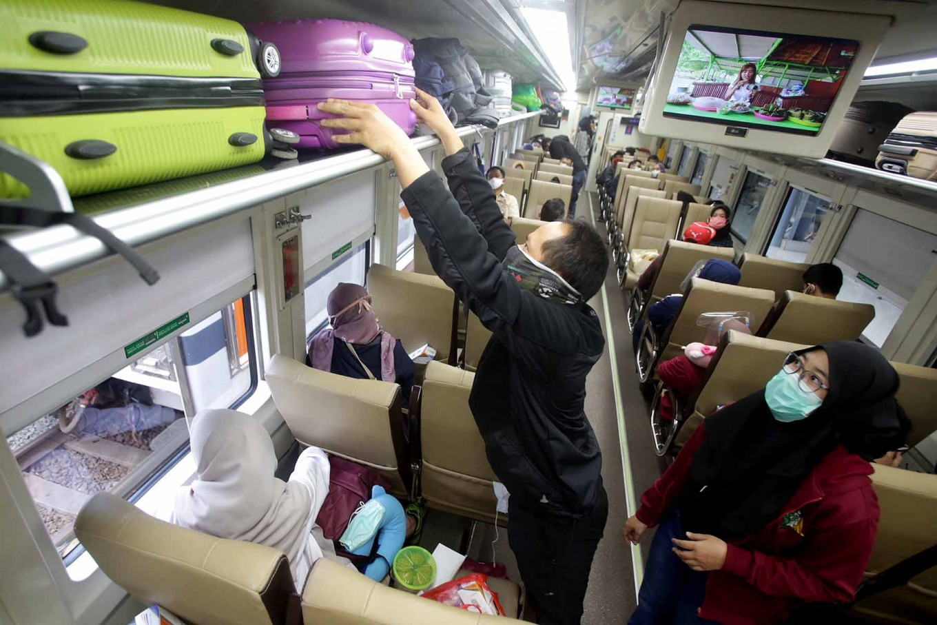 A passenger arranges his luggage on the Kertajaya train, serving the Jakarta–Surabaya route, at Senen Station in Jakarta on Oct. 27. Many people chose to travel during their extended holiday despite the risk of contracting the coronavirus. JP/Wendra Ajistyatama