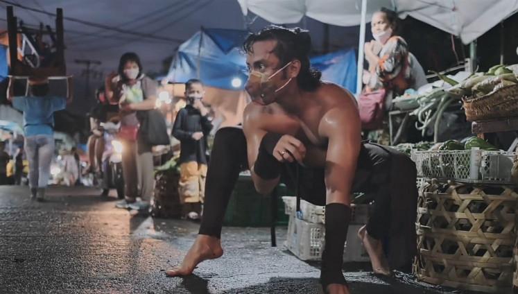 Among us: Balinese dancer I Putu Bagus Bang Sada Graha Saputra performs 'Buron Peken' (Market Animal), mimicking a dog in a wet market and interacting with onlookers.