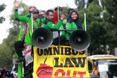 Members of labor unions take to the streets on a vehicle at Jl. Medan Merdeka Selatan near the Presidential Palace in Jakarta on Nov. 2, 2020. They were protesting against the controversial Job Creation Law and demanded an increase to the minimum wage in 2021. JP/Dhoni Setiawan