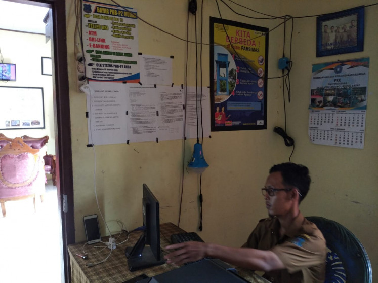 A village official operates a computer and charges his smartphone in Sungai Kayu Aro village using solar-generated electricity. The village used to run on diesel generators that only provided enough power for four light bulbs per home.