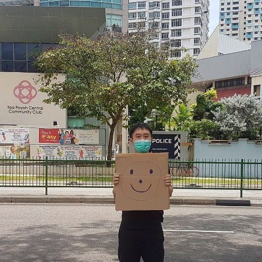 Singapore activist faces fine over one-man smiley face sign protest