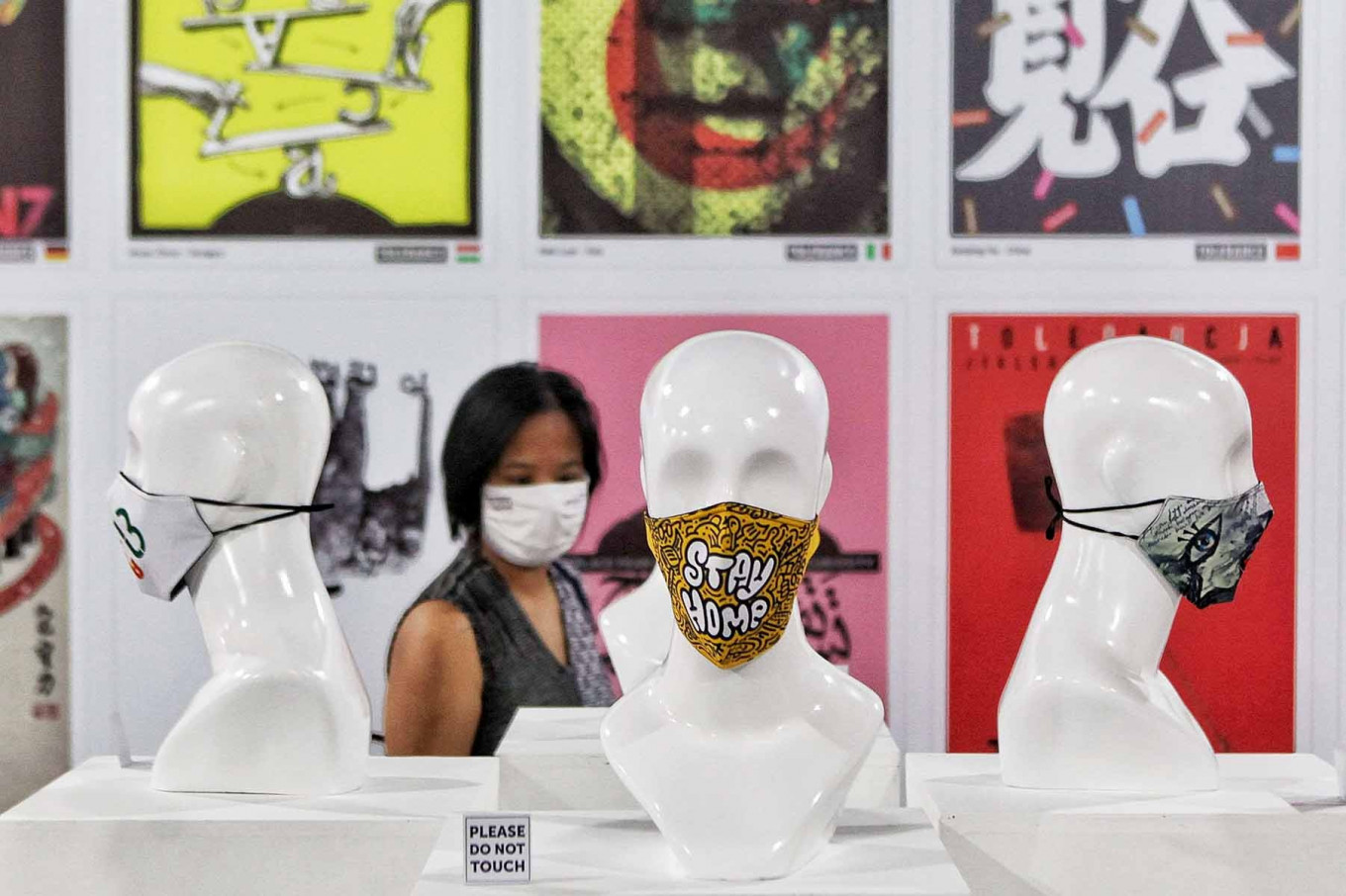 A visitor looks at posters and face masks displayed at an exhibition at Summarecon Mall Serpong in Tangerang, Banten. Coinciding with National Heroes Day on Nov. 10, the exhibition aims to spread the message that anyone can be a hero by wearing a mask and adhering to health protocols. JP/Seto Wardhana