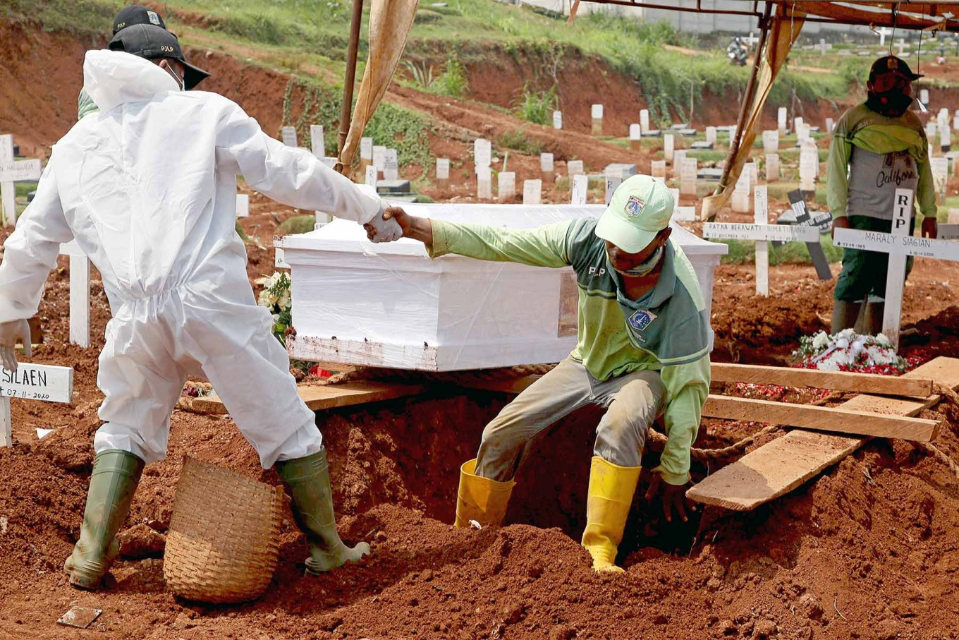 A grave worker helps his colleague out of the grave of a COVID-19 patient at Pondok Ranggon public cemetery in East Jakarta on Wednesday, Nov 12 The men had to widen the hole to make room for the coffin. JP/P.J.Leo