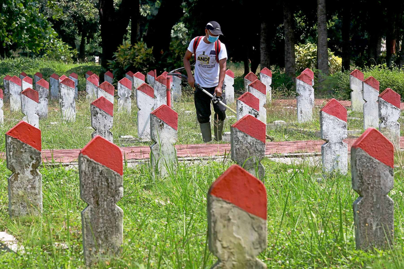 lham, 39, a caretaker at the Pahlawan Seribu Heroes Cemetery in South Tangerang, Banten, cuts weed around gravestones on Monday, Nov 9. Unlike previous years, the cemetery was closed during National Heroes Day on Nov. 10 due to the COVID-19 crisis. JP/Dhoni Setiawan.
