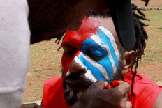 A Papuan Student Alliance (AMP) member has his face painted with the colors of the Bintang Kejora (Morning Star) flag during a protest on Jl. Medan Merdeka Barat, Central Jakarta, on Nov. 16. The protesters demanded that the government thoroughly investigate the killing of Papuan pastor Yeremia Zanambani in Intan Jaya, Papua, and withdraw military and police personnel from the country's easternmost province. JP/Dhoni Setiawan
