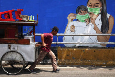A chicken porridge vendor pulls his cart past a COVID-19 mural on Jl. KH Abdullah Syafei in South Jakarta on Nov. 16. The number of confirmed COVID-19 cases soared after many celebrated a long weekend from Oct. 28 to Nov. 1. JP/P.J. Leo
