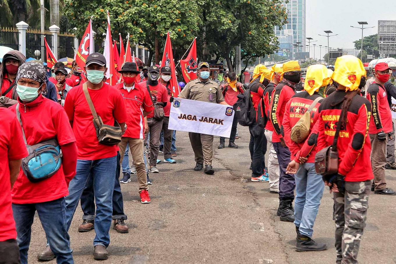 A Jakarta Public Order Agency (Satpol PP) officer holds up a banner on health protocols as workers protest the Job Creation Law in Jakarta on Nov. 17. The agency has urged protesters to wear masks and keep their distance to prevent the spread of COVID-19. JP/Seto Wardhana