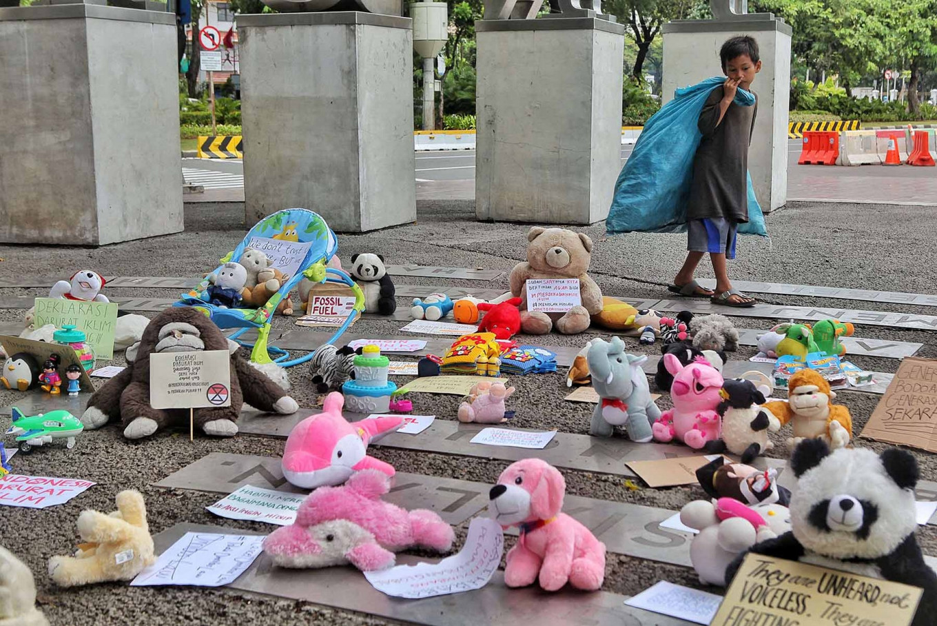 A boy with a bag of scavenged goods looks at toys displayed to commemorate World Children's Day in Jakarta on Nov. 20. The Extinction Rebellion (XR) group displayed hundreds of toys to represent Indonesian children and urged the government to do more to protect them. JP/Seto Wardhana
