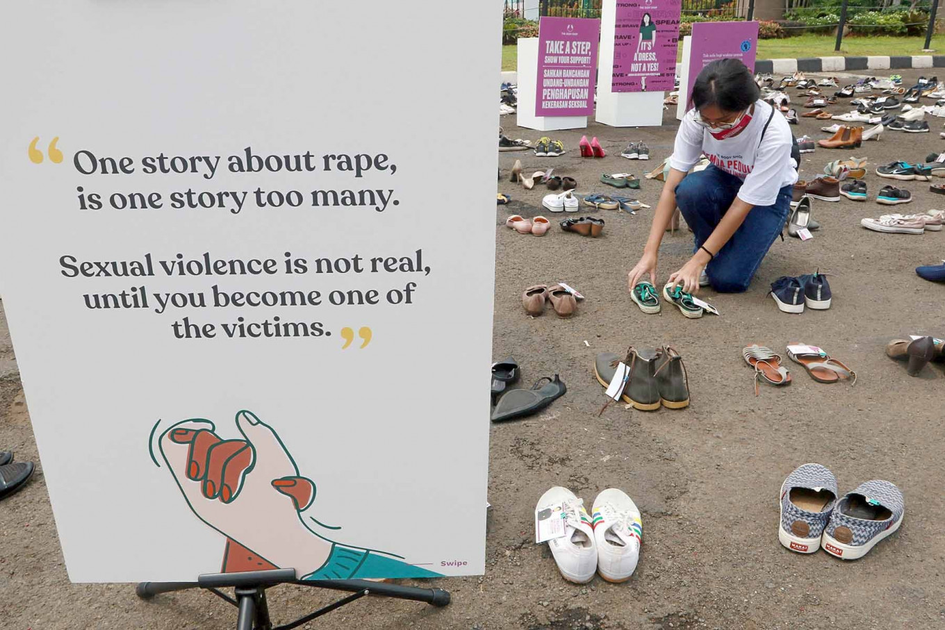 An activist arrange pairs of women's shoes at the House of Representatives complex in Central Jakarta on Nov. 25. The Shoes in Silence campaign, marking the International Day for the Elimination of Violence against Women, urged lawmakers to pass the sexual violence eradication bill. JP/Dhoni Setiawan
