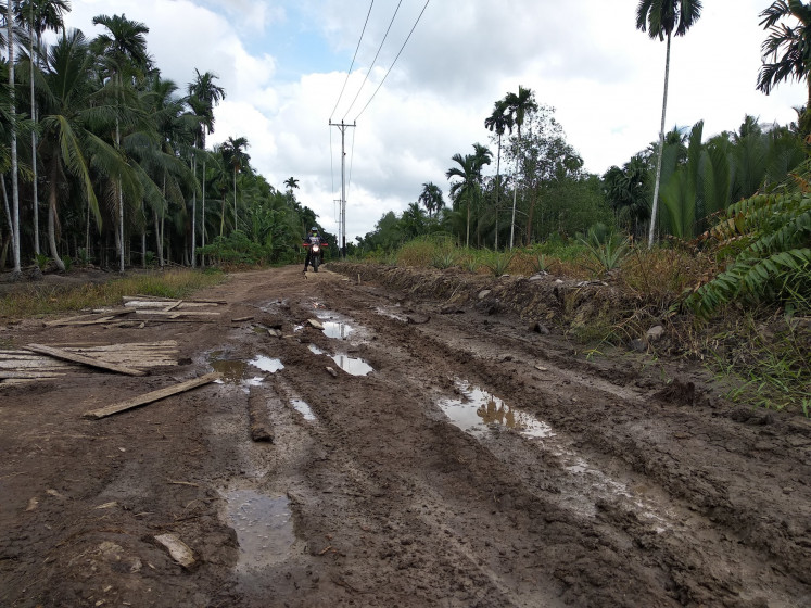 No paved road, no help: Muddy grooves line the road to Merbau village in Tanjung Jabung Timur, Jambi province. Despite the improvements in fire safety and prevention measures, the villagers  are worried they'll be on their own in the event of a fire disaster, due to the lack of a road for heavy vehicles.