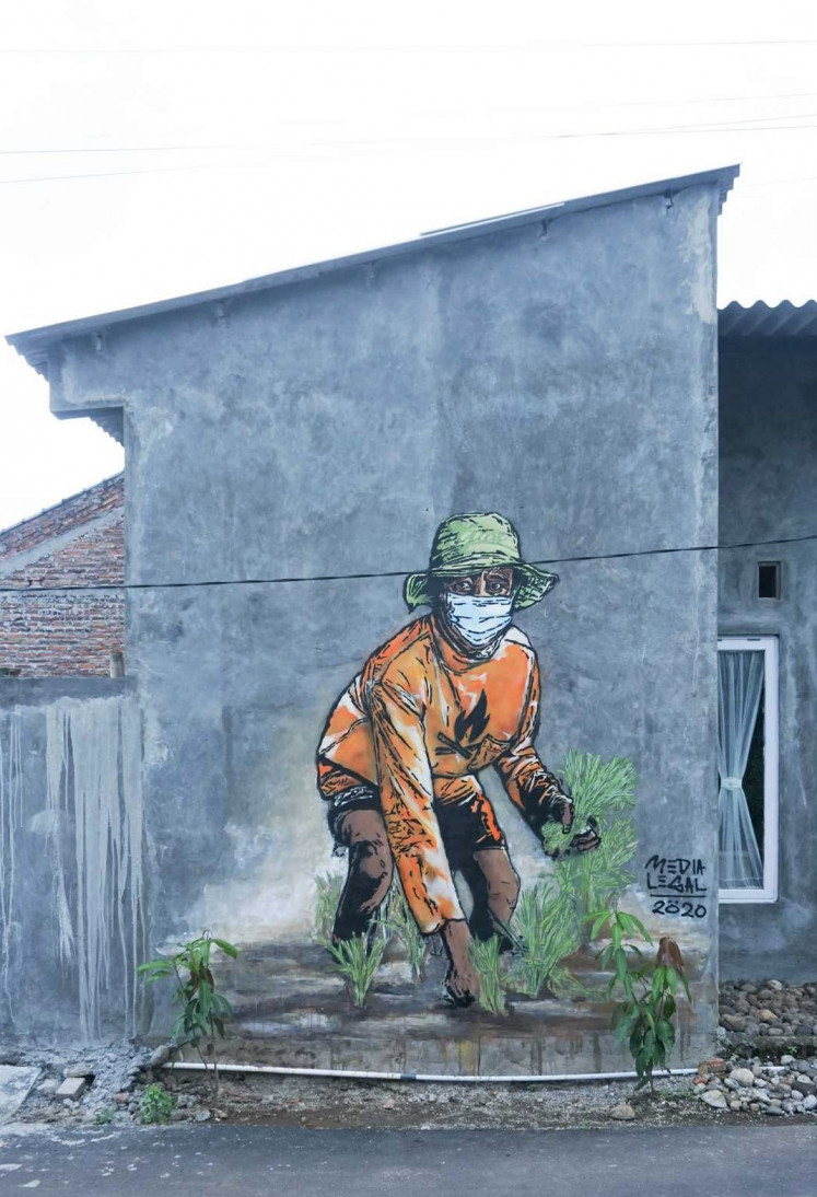 Safe farming: A mural shows a farmer planting paddy seedlings on a house wall in Kampung Sendangguwo. The mural, part of the biennial art project Penta Klabs by the artist collective Kolektif Hysteria, was displayed virtually at the National Gallery of Indonesia's digital exhibition platform.