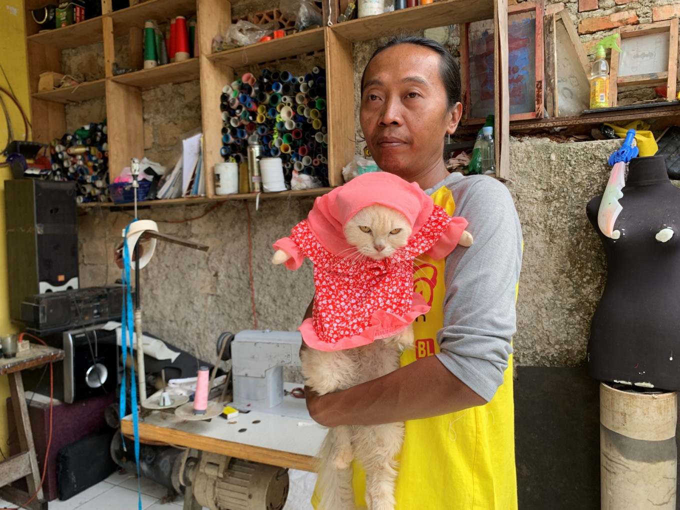 Fredi Lugina Priadi, 39, holds his cat wearing a cosplay costume in Bogor, on the outskirts of Jakarta, Indonesia, November 26, 2020. Reuters/Yuddy Cahya Budiman