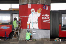 Graffiti artists embellish concrete pillars of the Cawang-Tanjung Priuk elevated toll road in East Jakarta on Dec. 4. Through the murals, the artists want to remind the public to adhere to health protocol. A day before, Indonesia shattered its COVID-19 daily record with more than 8,000 new cases. JP/P.J.Leo